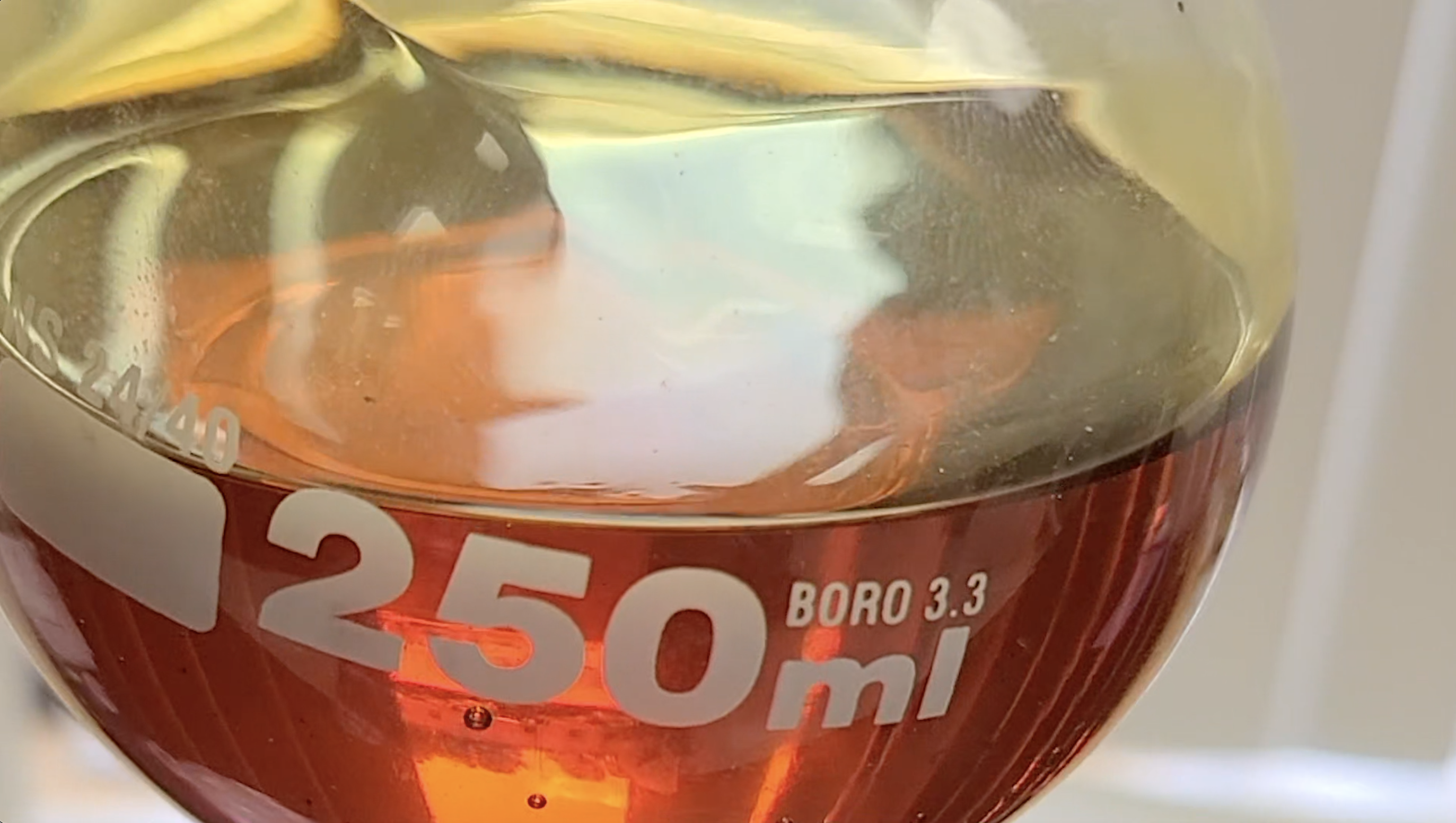 A glass beaker full of red-orange tinted CBD oil with 250ml markings visibile